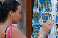 Beautiful woman  choosing souvenir postcards Stock Image
