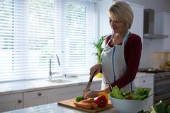 Beautiful woman chopping vegetables. In kitchen Stock Photos