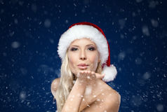 Beautiful woman in Christmas cap blows kiss royalty free stock photography