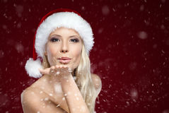 Beautiful woman in Christmas cap blows kiss Stock Image