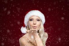 Beautiful woman in Christmas cap blows kiss Stock Photos