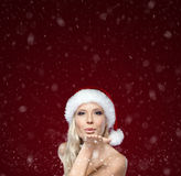 Beautiful woman in Christmas cap blows kiss Royalty Free Stock Photo