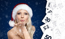 Beautiful woman in Christmas cap blows kiss to all purchasers stock photography
