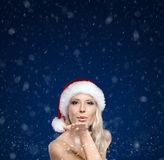 Beautiful woman in Christmas cap blows kiss Stock Photography