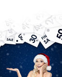 Beautiful woman in Christmas cap gestures palm up offer of the day Stock Photos