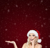 Beautiful woman in Christmas cap gestures palm up Royalty Free Stock Image