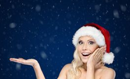 Beautiful woman in Christmas cap gestures palm up Stock Photo
