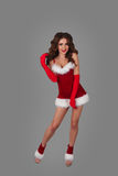 Beautiful woman in christmas dress  posing against grey background in full height Stock Photography