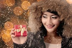 Beautiful woman with Christmas gift under snowfall Stock Photo