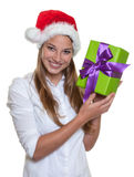 Beautiful woman with christmas hat has a gift in h Royalty Free Stock Image