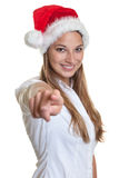 Beautiful woman with christmas hat pointing at camera Stock Photos