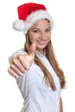 Beautiful woman with christmas hat showing thumb Stock Photography