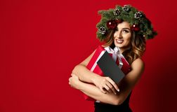 Beautiful woman with Christmas spruce fir wreath with cones and new year gift certificate present happy smiling. On red background stock photography