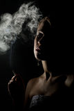 Beautiful woman with a cigarette in the dark. Silhouette of a beautiful woman with a cigarette in the dark royalty free stock photos