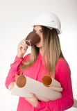 Beautiful woman civil engineer holding blueprints. Young female architect drinking coffee from brown cup Royalty Free Stock Photo