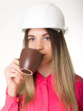 Beautiful woman civil engineer holding blueprints. Young female architect drinking coffee from brown cup Royalty Free Stock Photography