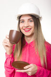 Beautiful woman civil engineer holding blueprints. Young female architect drinking coffee from brown cup Stock Photography