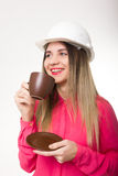 Beautiful woman civil engineer holding blueprints. Young female architect drinking coffee from brown cup Royalty Free Stock Images