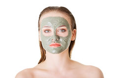 Beautiful woman with clay facial mask, isolated on white Royalty Free Stock Photos