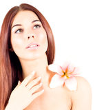 Beautiful woman with clean skin and with flower looks up. Facial result. Stock Image