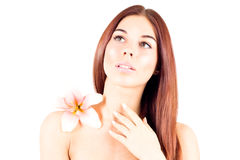 Beautiful woman with clean skin and with flower looks up. Facial result. Royalty Free Stock Photography