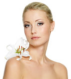 Beautiful woman with  clean skin and white flower. Beautiful young woman with fresh clean skin and white flower on shoulder - isolated Stock Photo