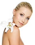Beautiful woman with  clean skin and white flower. Beautiful young woman with fresh clean skin and white flower on shoulder - isolated Royalty Free Stock Image