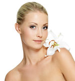Beautiful woman with  clean skin and white flower. Beautiful young woman with fresh clean skin and white flower on shoulder - isolated Royalty Free Stock Photos