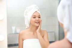 Beautiful woman with clean towels near mirror. In bathroom royalty free stock photos