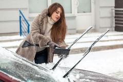 Beautiful woman cleaning car with brush after blizzard Royalty Free Stock Photography
