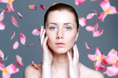 Beautiful woman with clear skin and falling rose petals Stock Photo