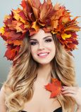 Beautiful woman with clear skin, healty curly hairstyle and autumn leaves.  royalty free stock image