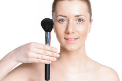 Beautiful woman with clear skin holds cosmetic brush Royalty Free Stock Image