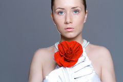 Beautiful woman with clear skin, red rose and perl necklace Royalty Free Stock Images