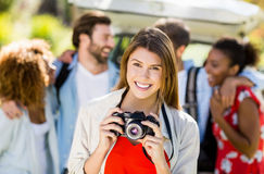 Beautiful woman clicking a photo from camera in park Royalty Free Stock Images