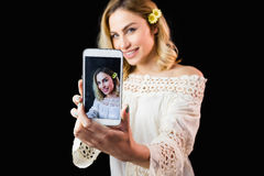 Beautiful woman clicking photo from mobile phone against black background Royalty Free Stock Images