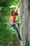 Beautiful woman climber climbing steep rock with rope royalty free stock photography