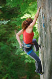 Beautiful woman climber climbing steep rock with rope. Young sporty female climbing steep natural rock wall in summer time. Girl is hanging on one hand and Royalty Free Stock Photography