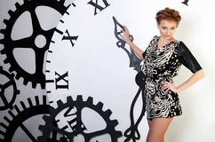 The beautiful woman on clockwork background Royalty Free Stock Photo