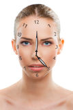 Beautiful woman close up with a clock. Over white background Royalty Free Stock Photos