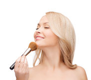 Beautiful woman with closed eyes and makeup brush Stock Photography