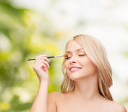 Beautiful woman with closed eyes and makeup brush Royalty Free Stock Images