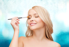 Beautiful woman with closed eyes and makeup brush Royalty Free Stock Photography
