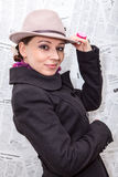 Beautiful woman in coat and hat against newspapers background Stock Photo