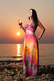 Beautiful woman with a cocktail on the beach. Beautiful woman with a cocktail and a robe on the beach and a wonderful sunset Royalty Free Stock Image