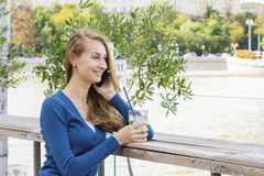 Beautiful Woman with cocktail in cafe mobile phone speaking. Royalty Free Stock Images