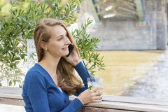 Beautiful Woman with cocktail in cafe mobile phone speaking. Royalty Free Stock Image