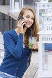 Beautiful Woman with cocktail in cafe mobile phone speaking. Royalty Free Stock Photography
