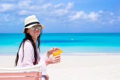 Beautiful woman with cocktail in hand on beach Stock Photo