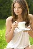 Beautiful woman with coffee. Girl in a meadow enjoying the sun royalty free stock image
